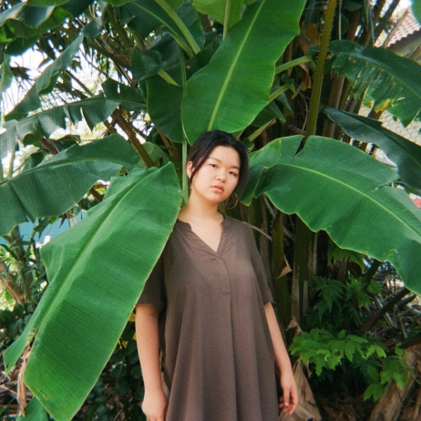A photo of Shin Ling posing in front of a banana tree.